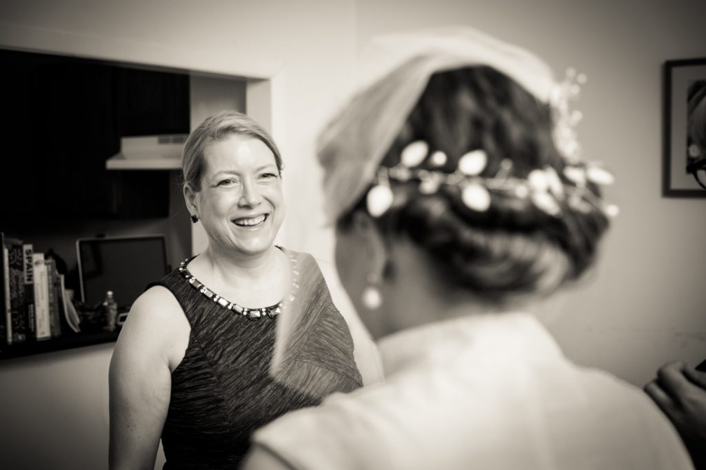 Black and white photo of mother looking at bride in wedding dress