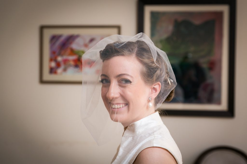 Smiling bride wearing birdcage headpiece