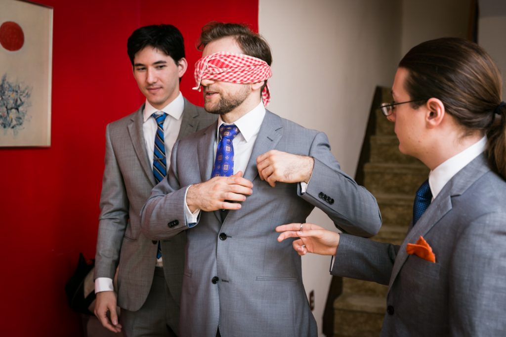 Blindfolded groom and two groomsmen before wedding