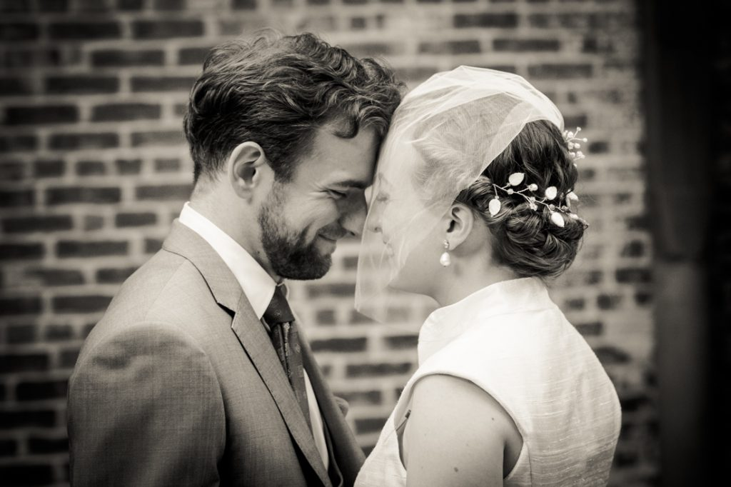 Black and white photo of bride and groom touching foreheads