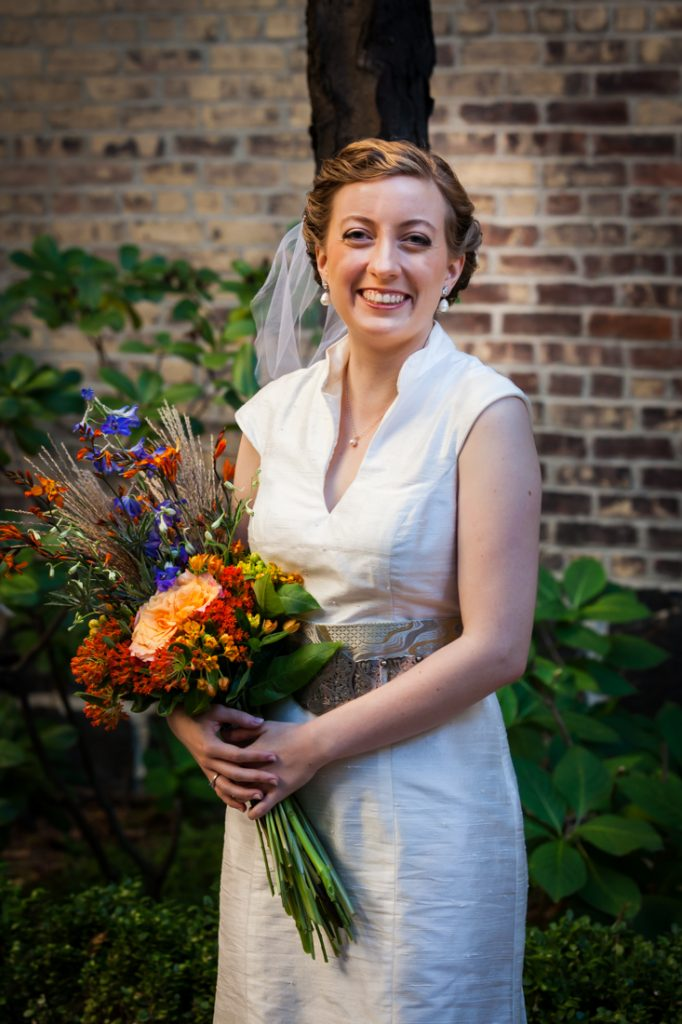 Portrait of bride wearing birdcage headpiece and holding flower bouquet