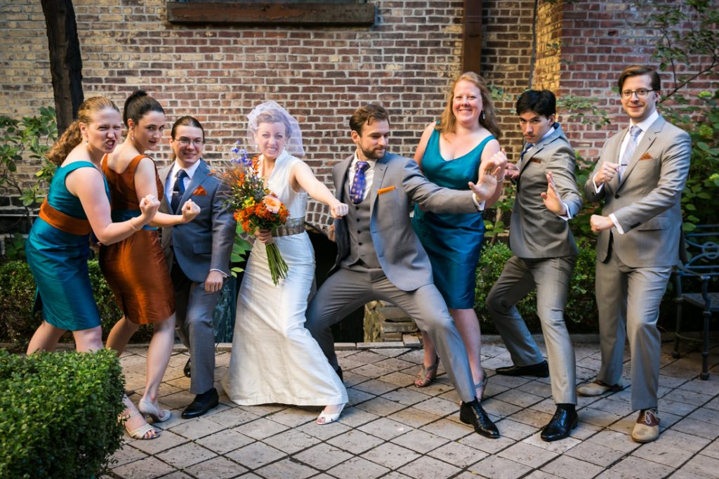 Bridal party in church patio doing martial arts pose