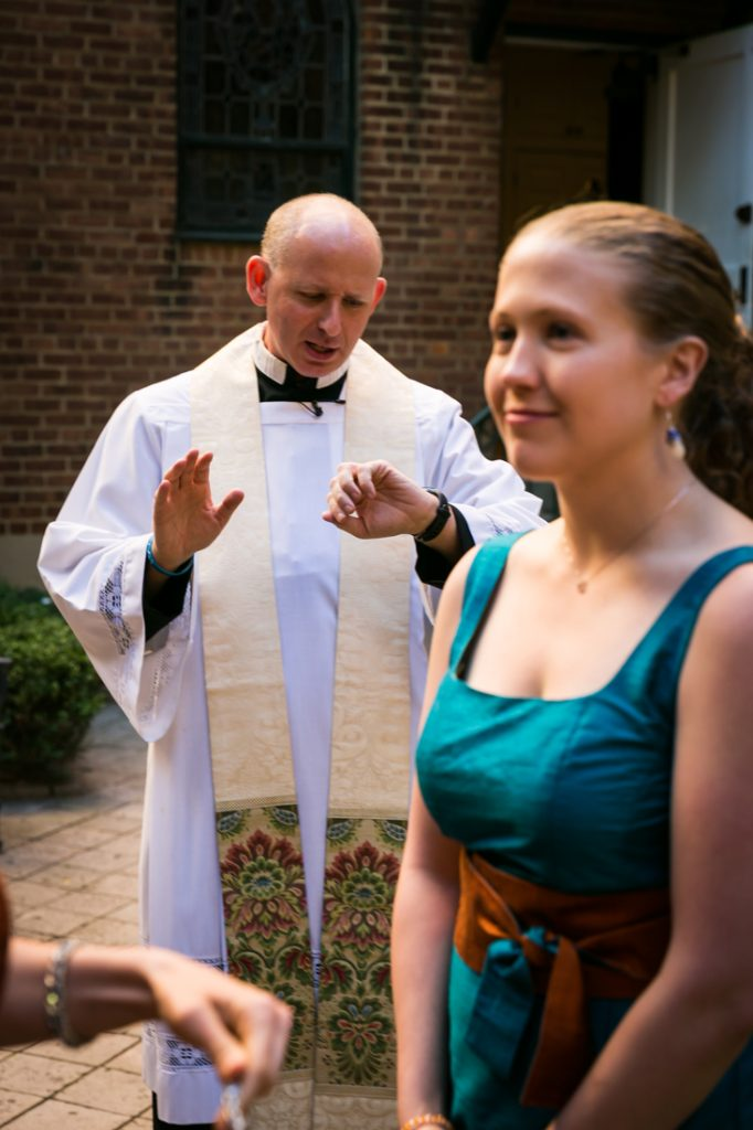 Priest looking at watch with bridesmaid
