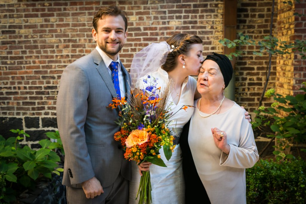 Bride kissing grandmother with groom