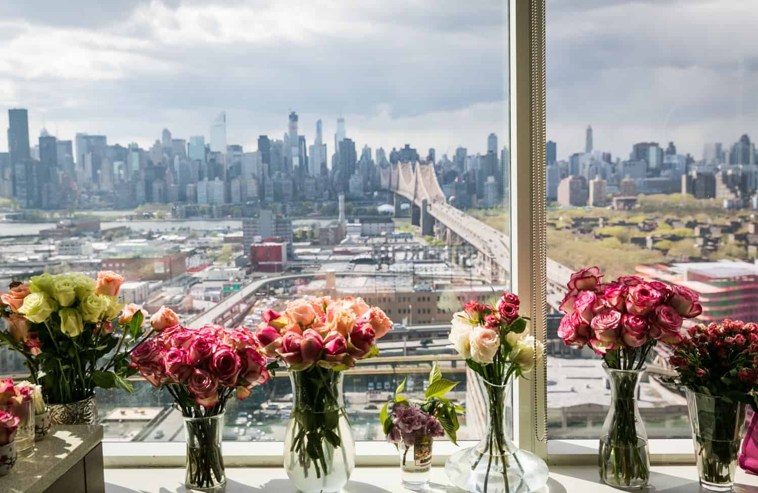 Vases of flowers on windowsill with NYC skyline in background