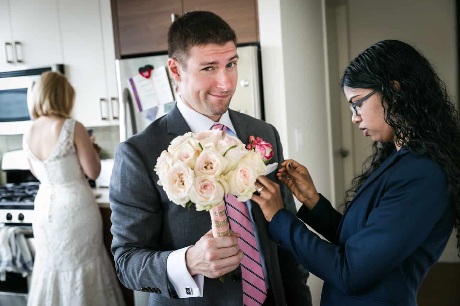 Groom holding bride's bouquet and having pocket square adjusted