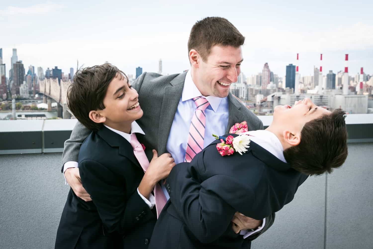 Groom and two young boys clowning around on roof