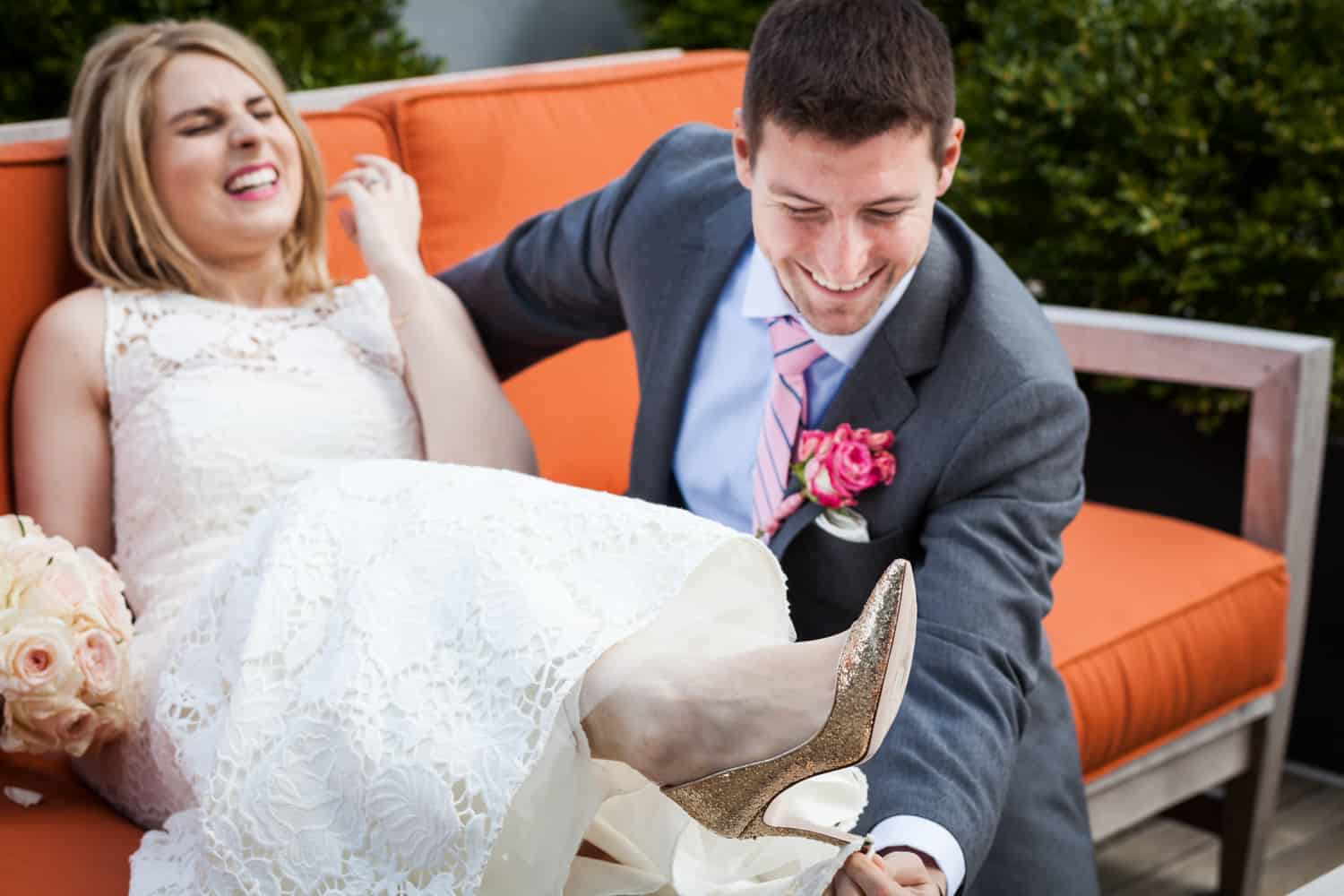 Groom getting train of bride's dress unhooked from her heel