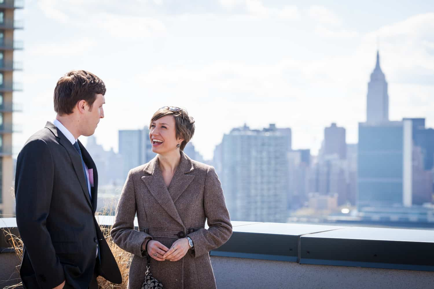 Couple talking on roof of building with Empire State Building in background