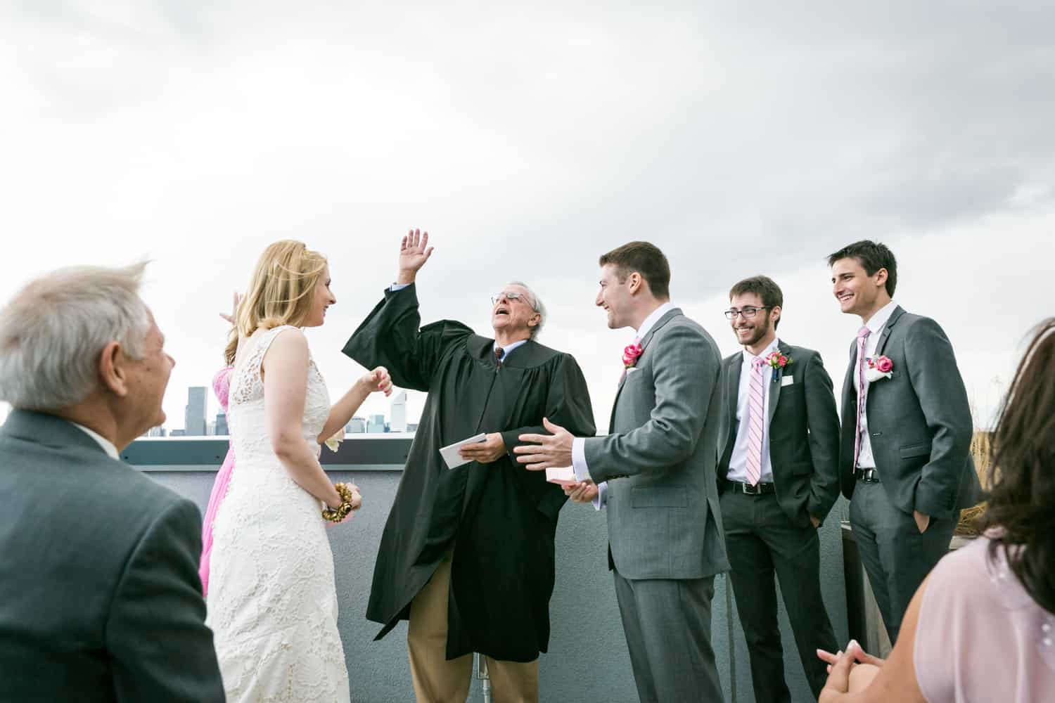 Officiant with hand in air during rooftop wedding ceremony