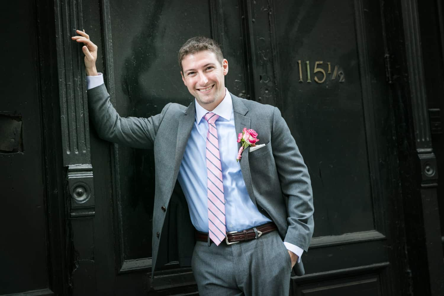 Groom leaning against wall in SoHo