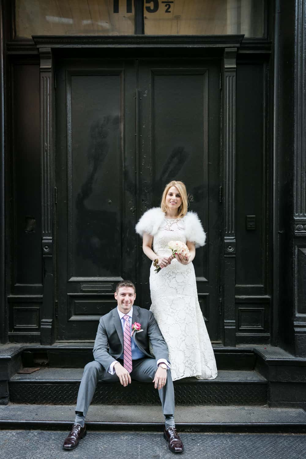 Bride and groom posed on stoop in Soho
