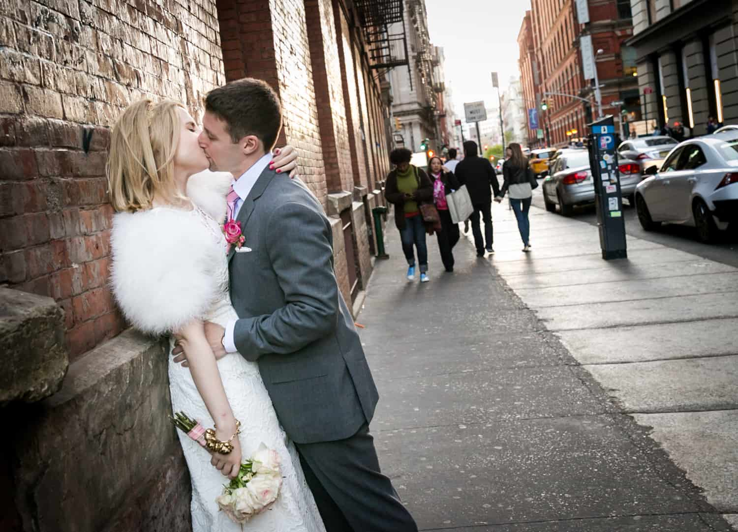 Bride and groom kissing against brick wall in Soho