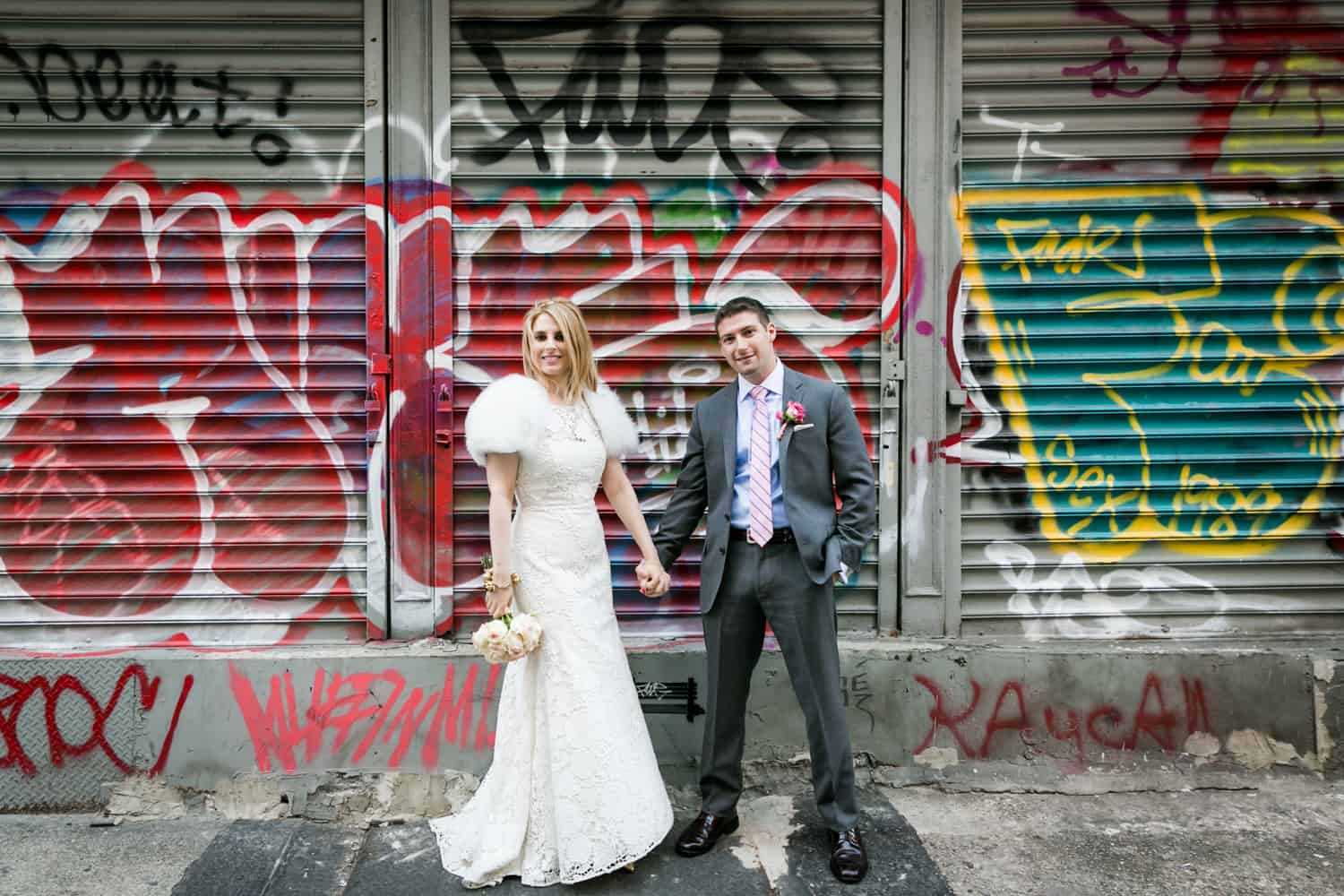 Bride and groom holding hands in front of graffiti covered metal gate