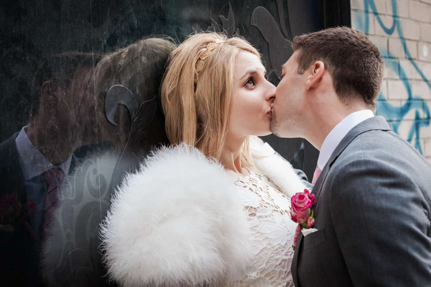 Bride and groom kissing against window