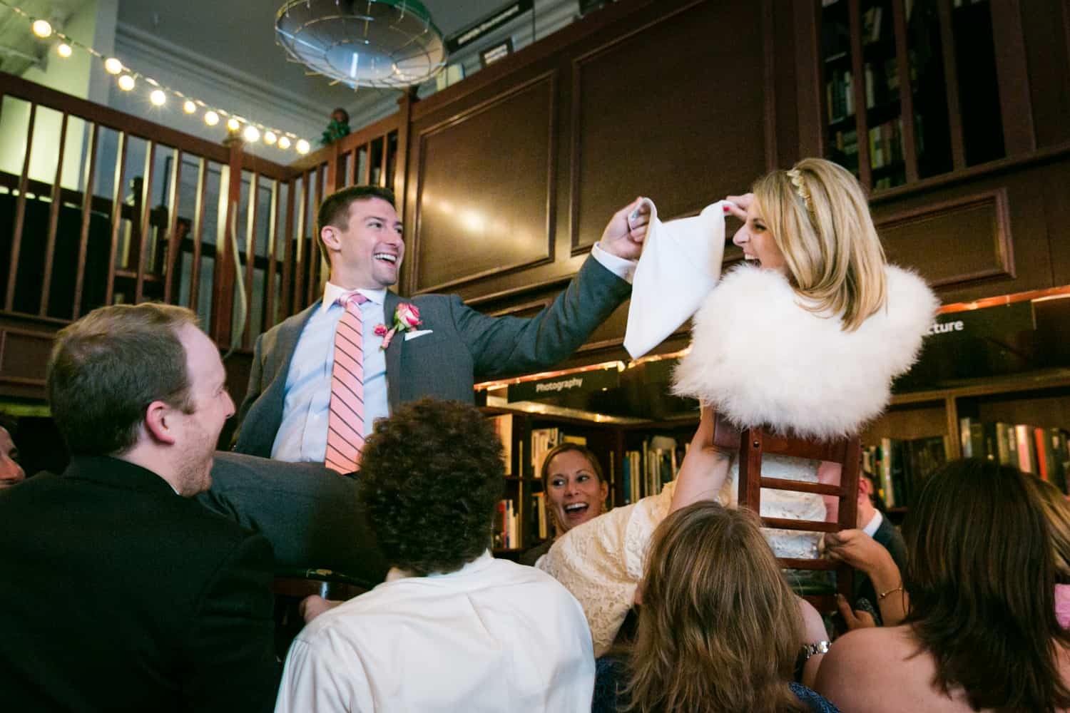 Bride and groom lifted up on chairs during hora dance at a Housing Works wedding