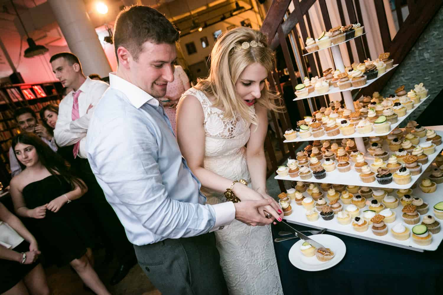 Bride and groom cutting mini cupcakes at a Housing Works wedding