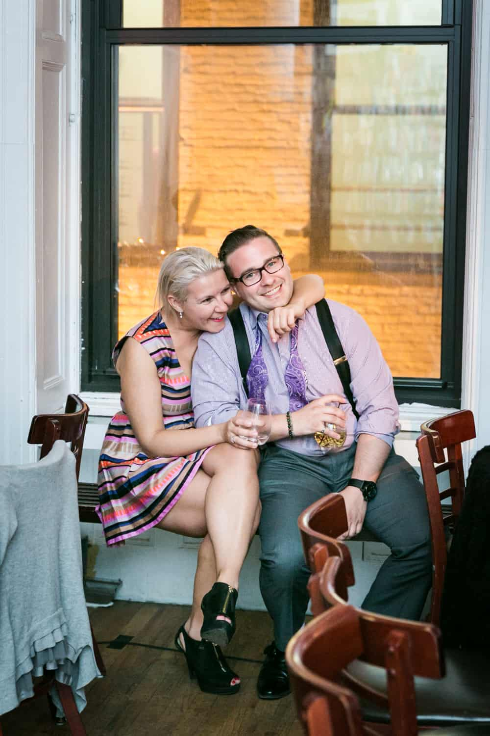 Couple hugging on windowsill at a Housing Works wedding