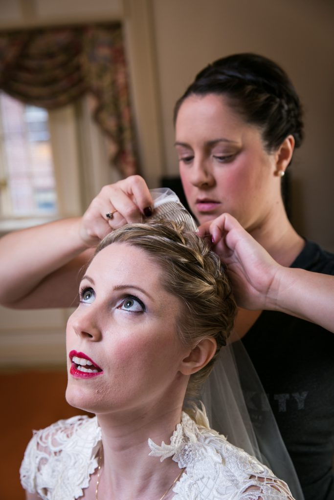 Bridesmaid attaching veil to bride