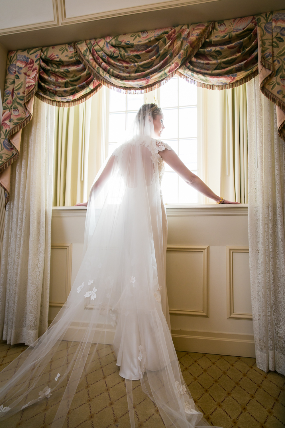 Bride wearing veil looking out window