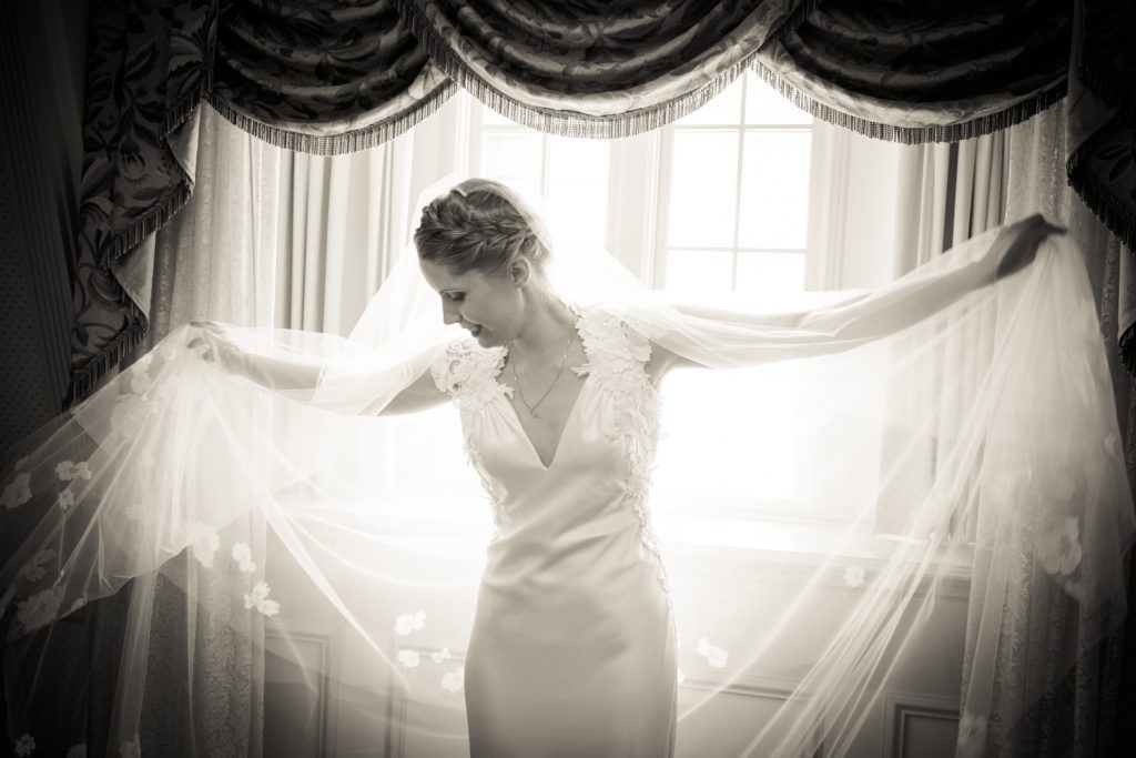 Black and white photo of bride playing with veil in front of window