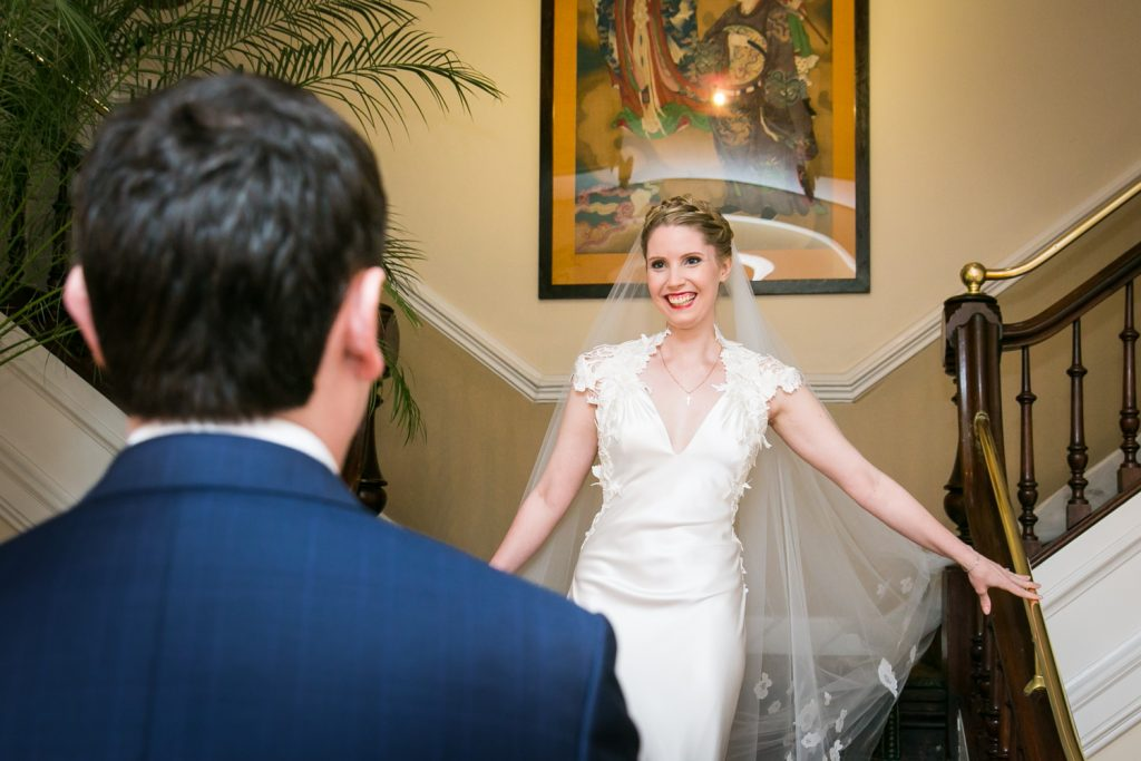 Bride walking down stairs to groom for the first time