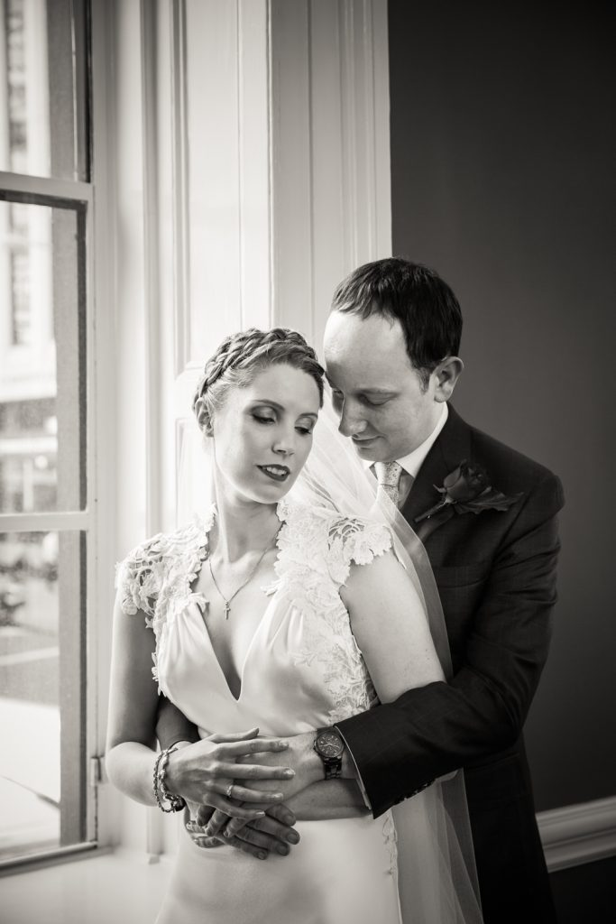 Black and white photo of groom hugging bride in front of window