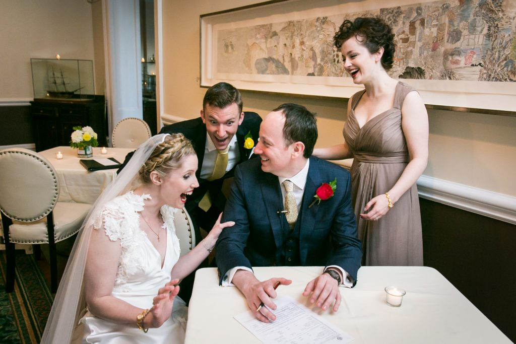 Bridal party laughing after signing wedding license