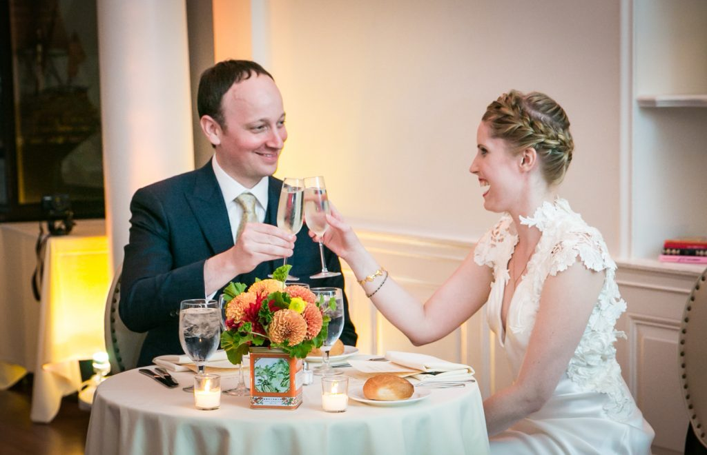 Bride and groom toasting champagne glasses at sweetheart table