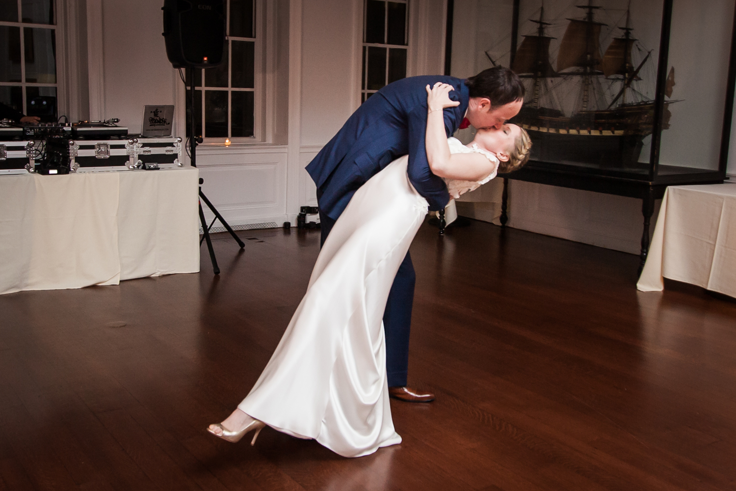 Groom dipping and kissing bride during first dance