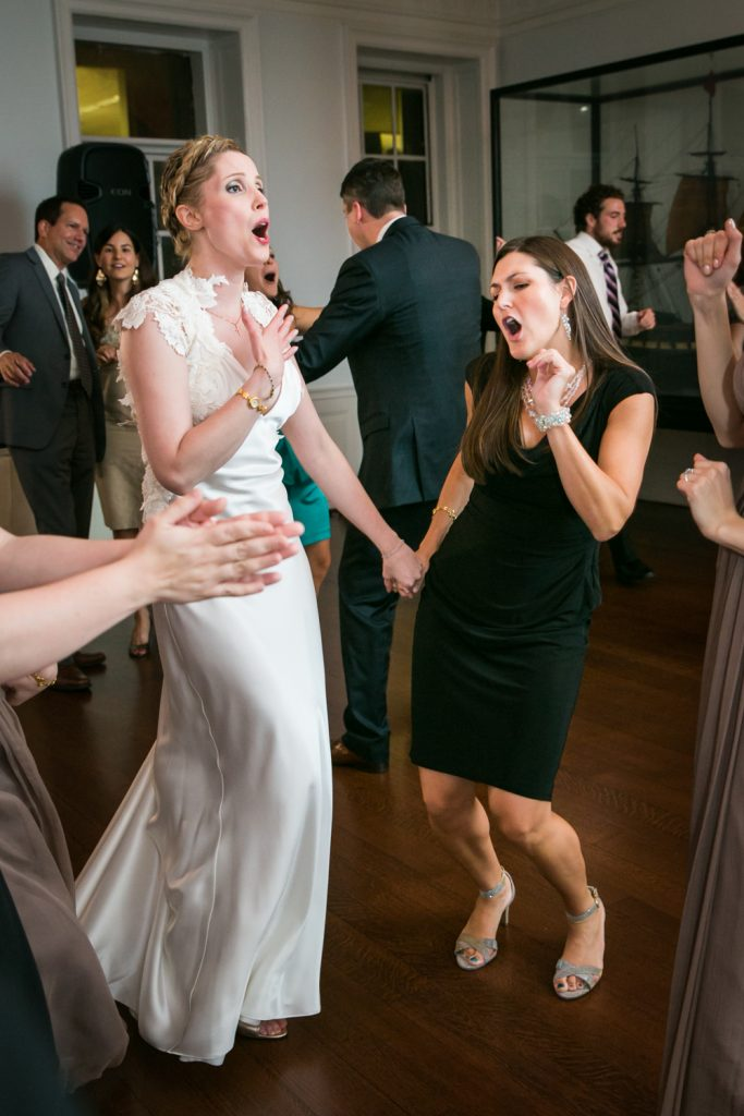 Bride holding hands with female guest and singing