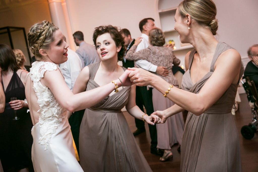 Bride holding hands and dancing with girlfriends