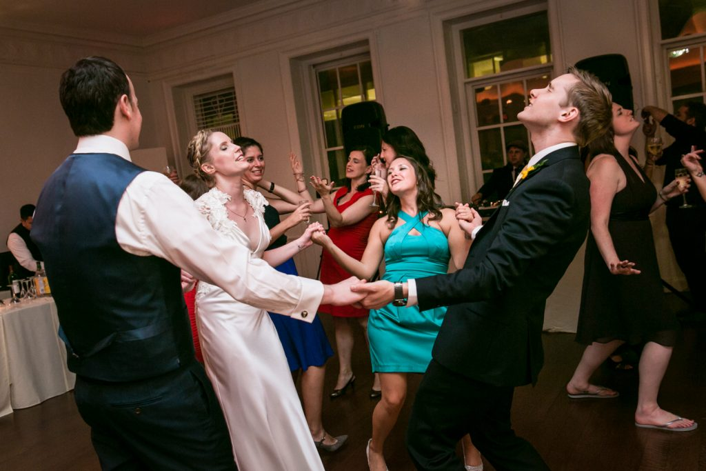 Bride and groom dancing with guests in a circle