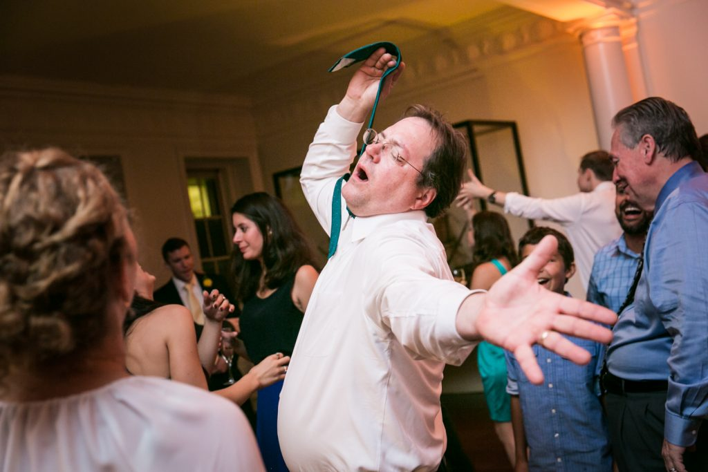 Man dancing while holding up his tie