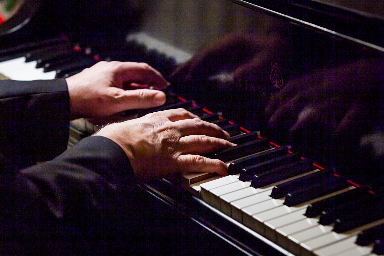 Close up on male hands playing the piano at a Lotos Club engagement party