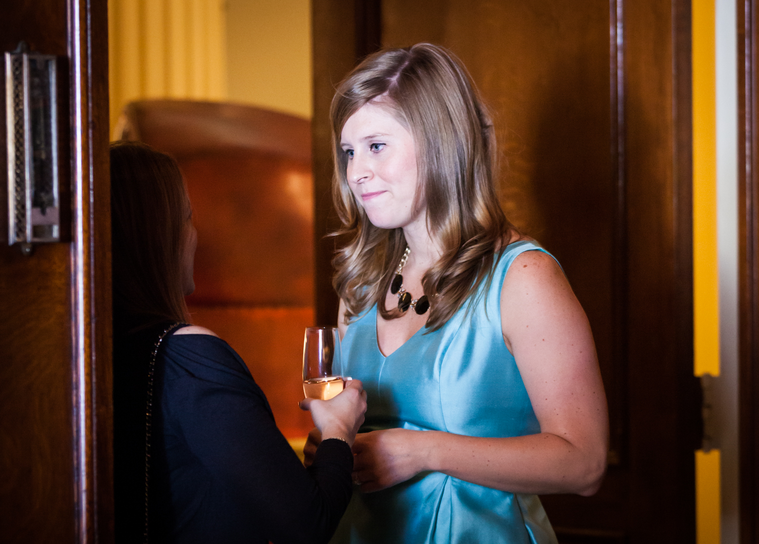Woman in blue dress listening to guest at a Lotos Club engagement party