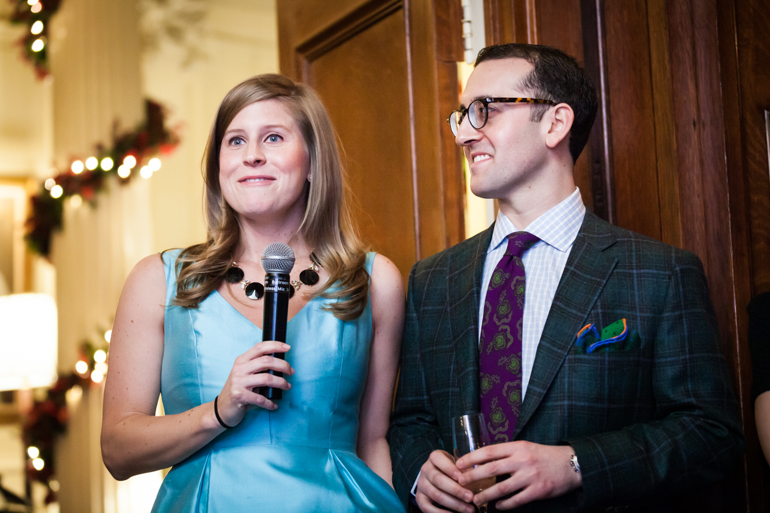 Woman in blue dress holding microphone next to man at a Lotos Club engagement party