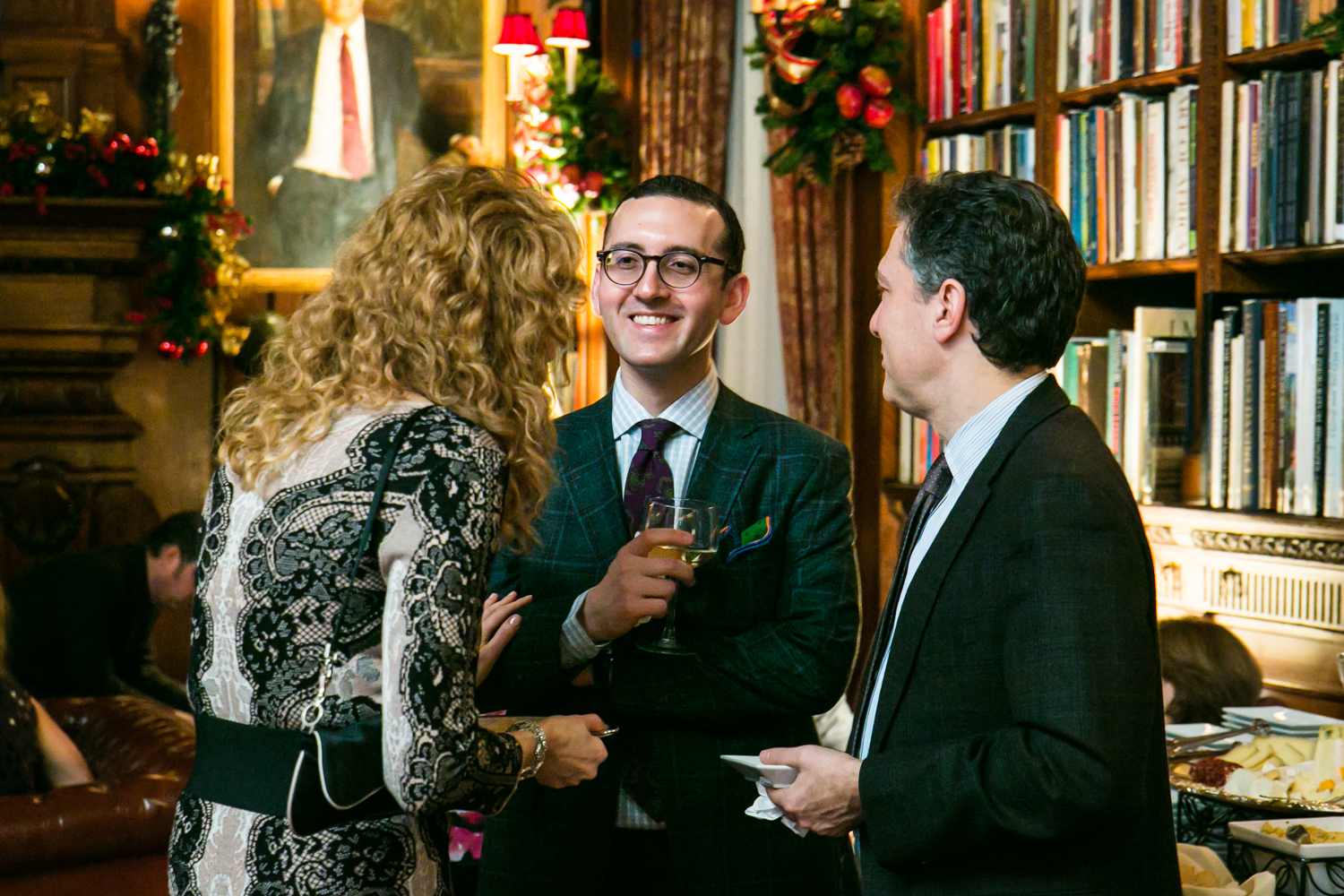 Groom and guests talking in library at a Lotos Club engagement party