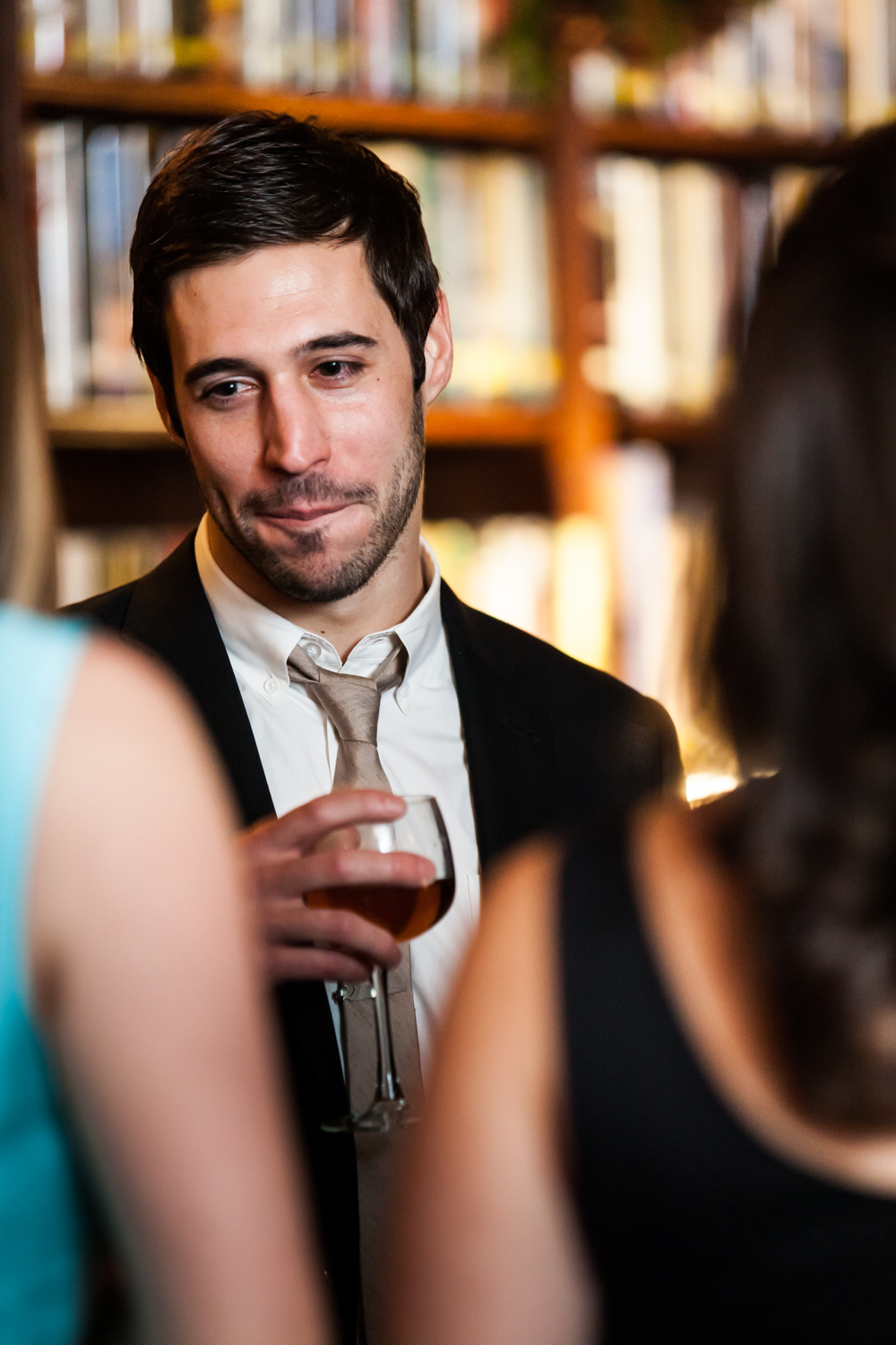 Man holding wine glass and listening to guests