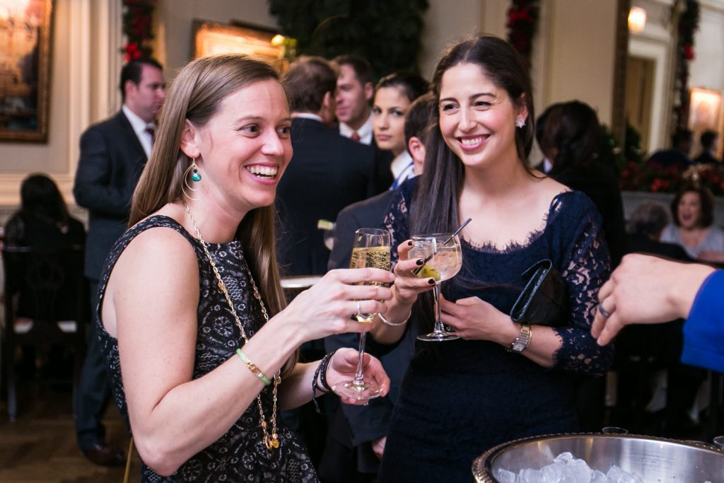 Two female guests holding wine glasses at a Lotos Club engagement party