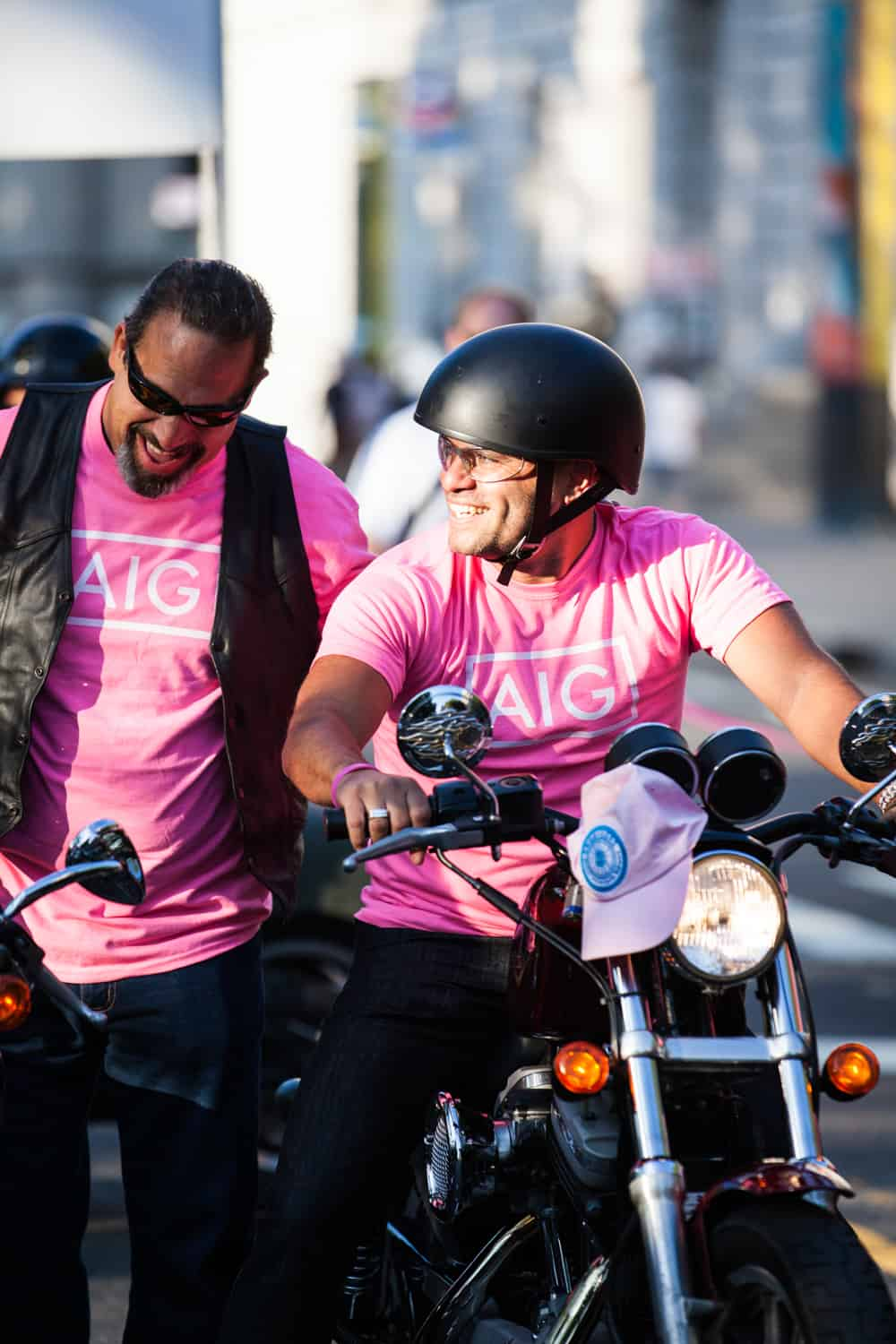 NYC Race for the Cure photos of man on motorcycle with helmet laughing with another anotherman