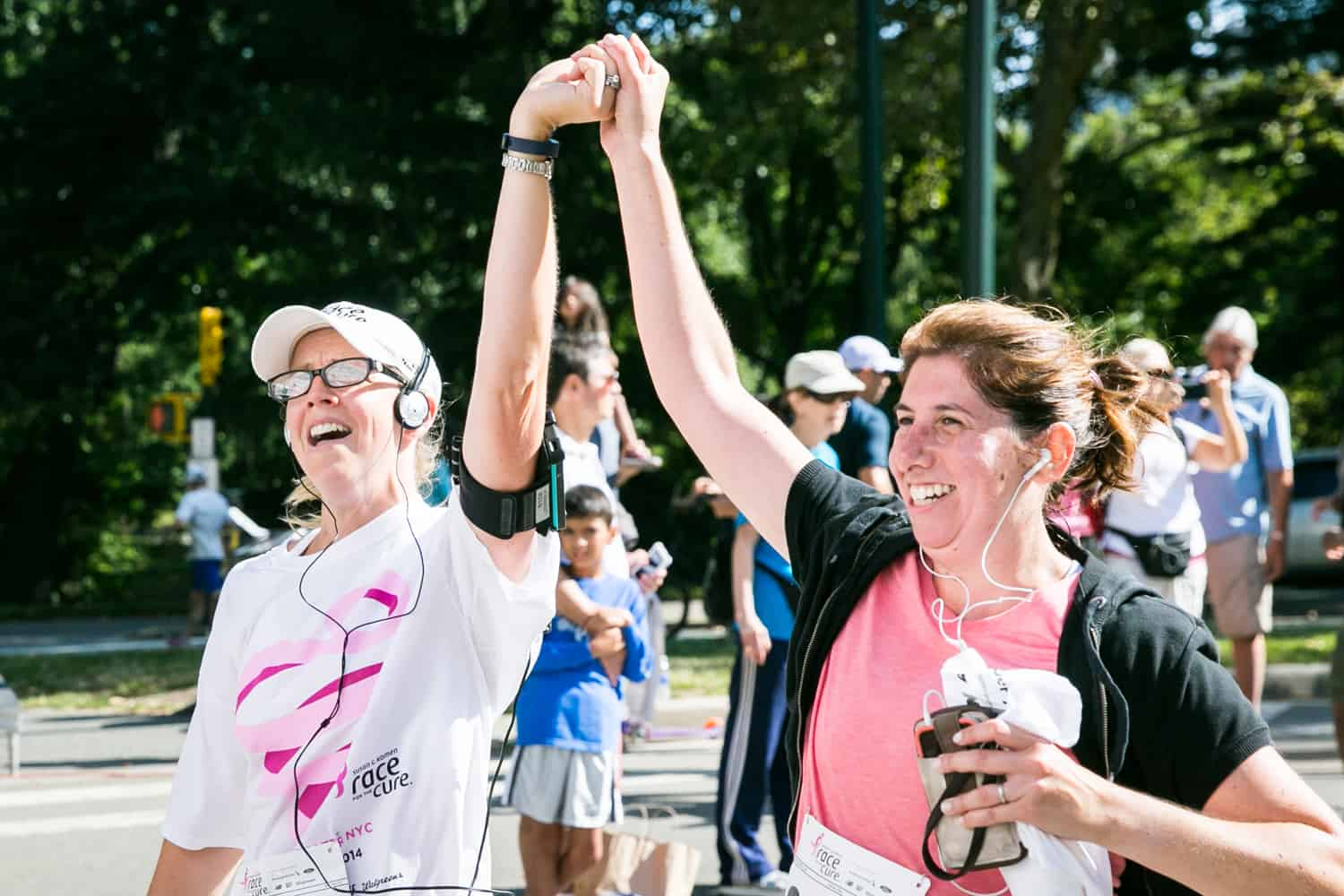 NYC Race for the Cure photos of two women crossing finish line with hands held in air
