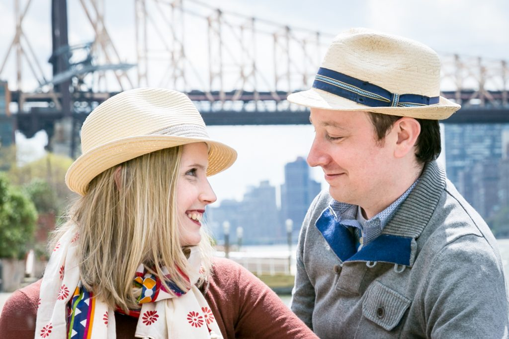 Couple wearing hats and looking at each other with Queensborough Bridge in background