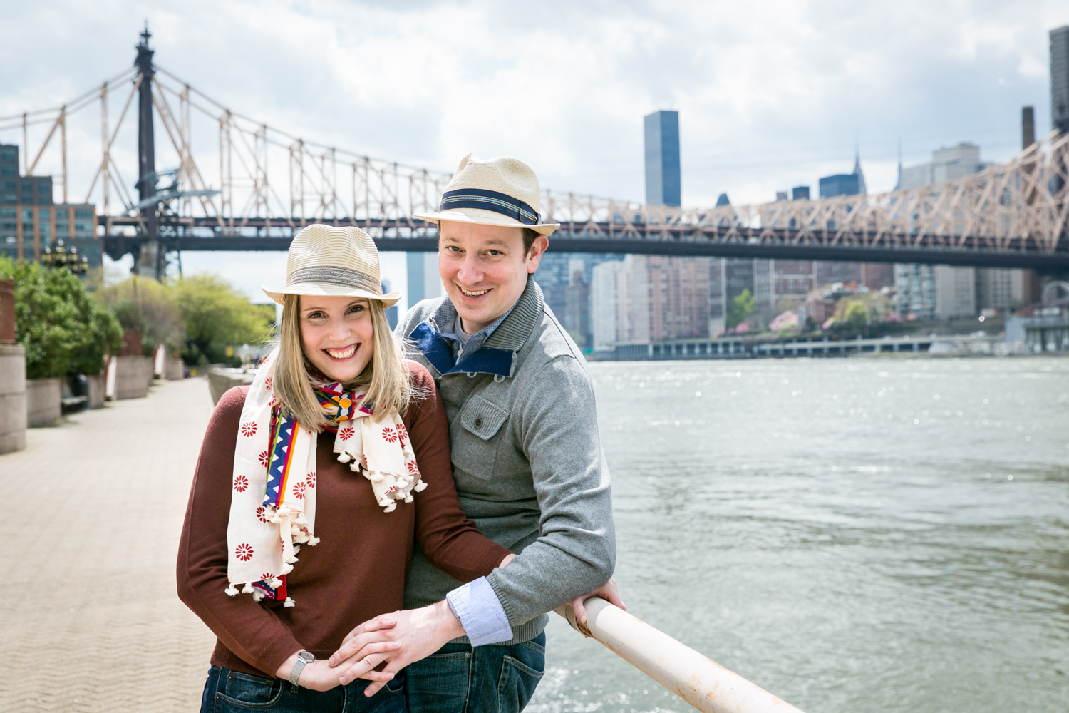 Couple leaning on railing with Queensborough Bridge in background during a Roosevelt Island engagement portrait session