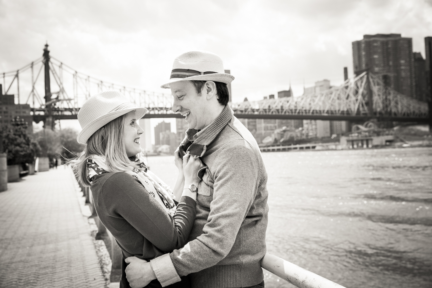 Black and white photo of couple wearing hats and looking at each other with Queensborough Bridge in background