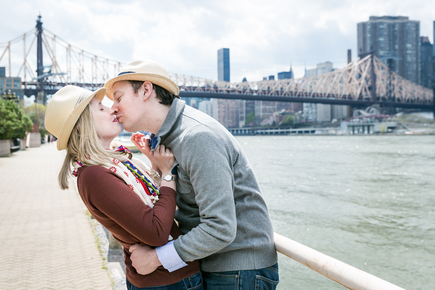 Couple kissing against railing with Queensborough Bridge in background