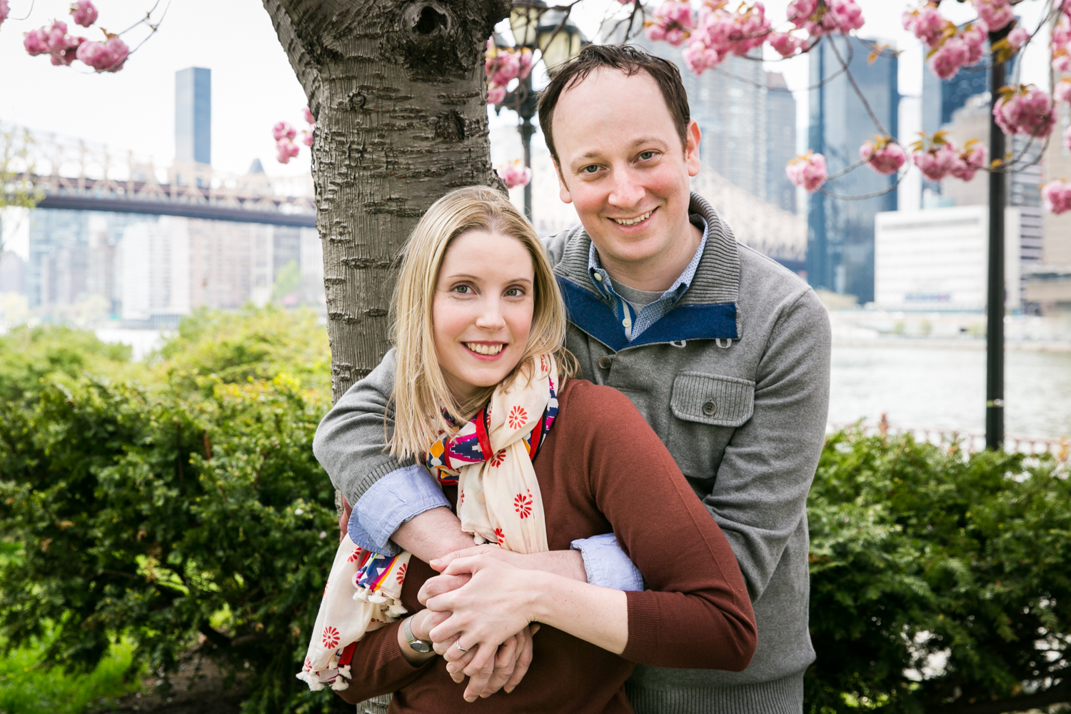 Couple standing under cherry blossom tree during a Roosevelt Island engagement portrait session