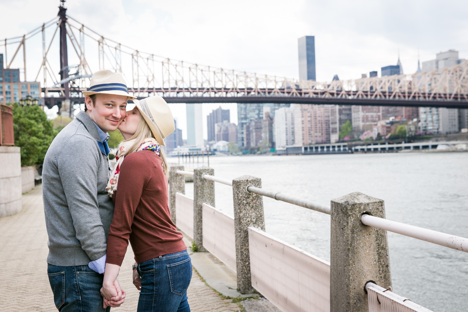 Woman kissing man on cheek during a Roosevelt Island engagement portrait session