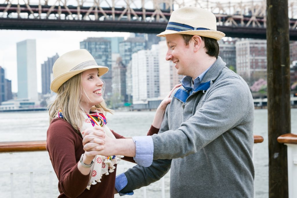 Couple dancing with Queensborough Bridge in background during a Roosevelt Island engagement portrait session