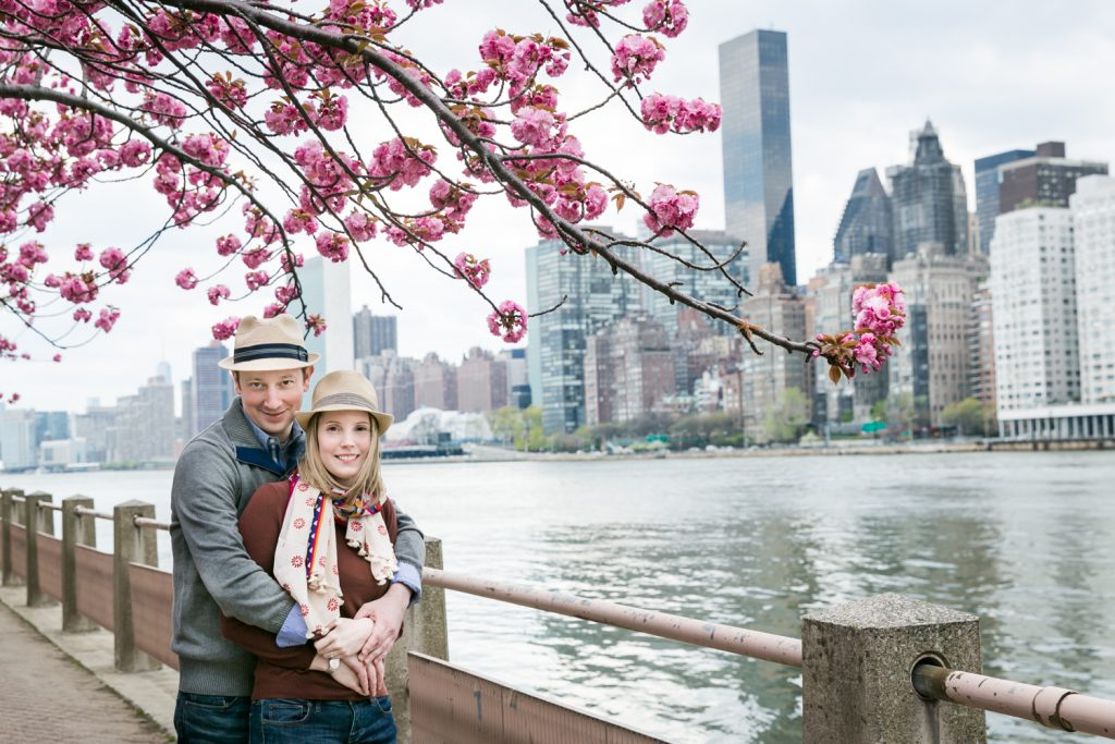Couple hugging with cherry blossom branches overhead during a Roosevelt Island engagement portrait session